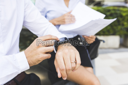 businessman with smartwatch and businesswoman with