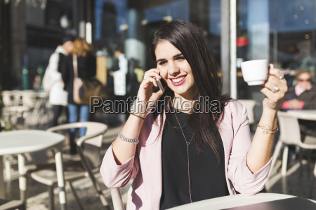 smiling young businesswoman on cell phone