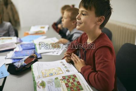 portraet eines laechelnden schuelers im unterricht