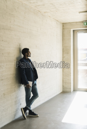 businessman standing at concrete wall looking