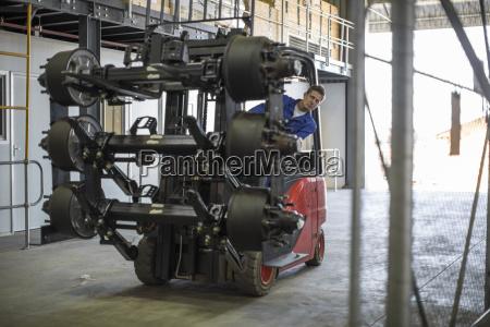 arbeiter bewegt ausruestung auf gabelstapler