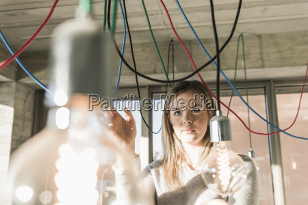 young businesswoman in office examining cables