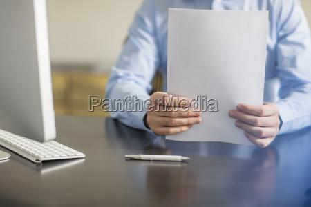 geschaeftsmann der am schreibtisch mit dokumenten