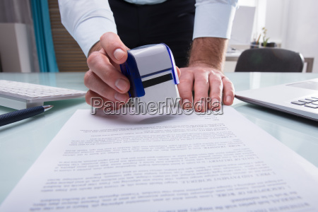 businessman stamping approved on document