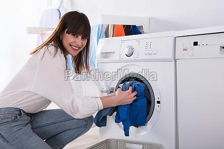 woman putting dirty cloth into washing