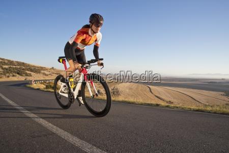 weibliches radfahrerreit rennrad auf sonniger offener