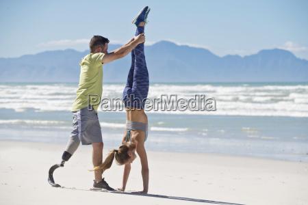 man wearing prosthetic blade helping woman