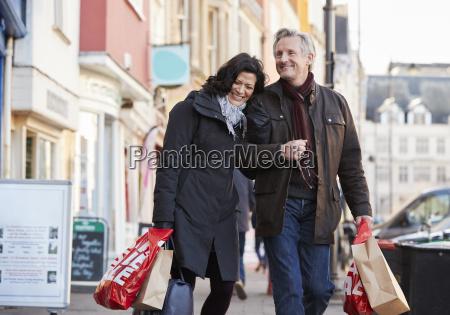 mature couple enjoying shopping in city