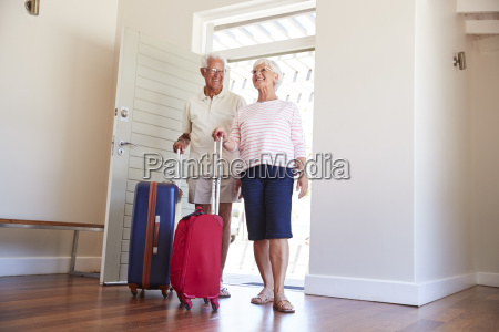 senior couple arriving at summer vacation