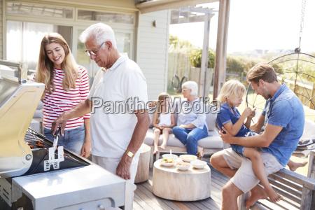 multi generation family enjoying cooking barbecue