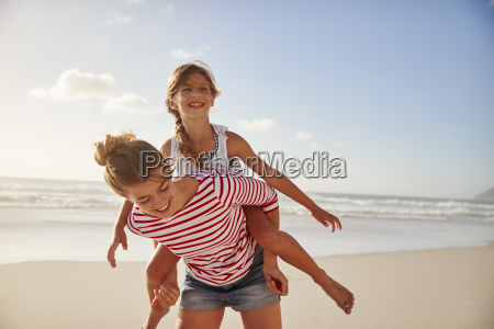 mother carrying daughter on shoulders on