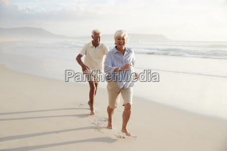 senior retired couple running along summer