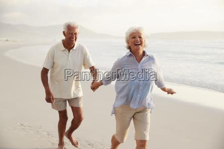 senior retired couple running along beach