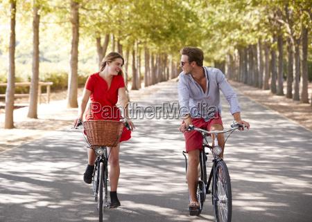 couple riding bikes on an empty