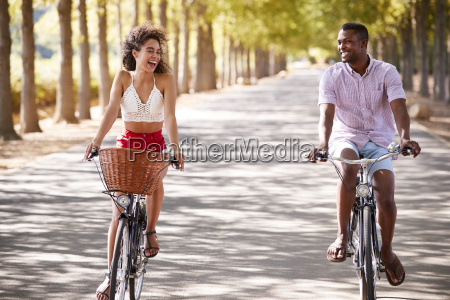 laughing young couple riding bicycles on