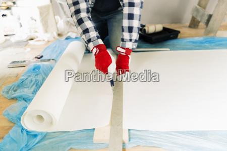 handwerker arbeiter messen tapete zu schneiden