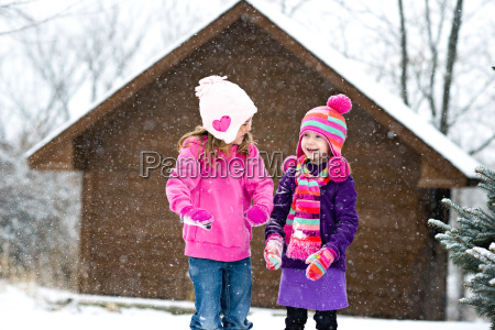 happy sisters playing with snow while