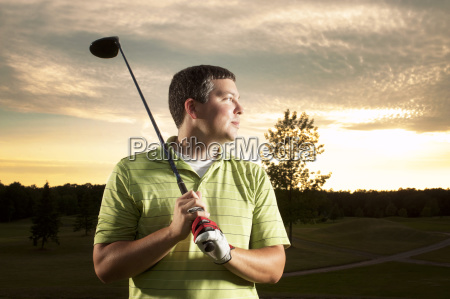 thoughtful man holding golf club against