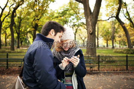 young couple using phone while standing