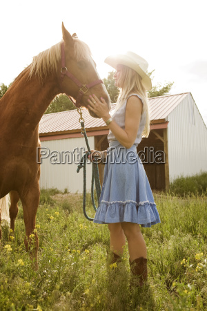 side view of cowgirl stroking horse