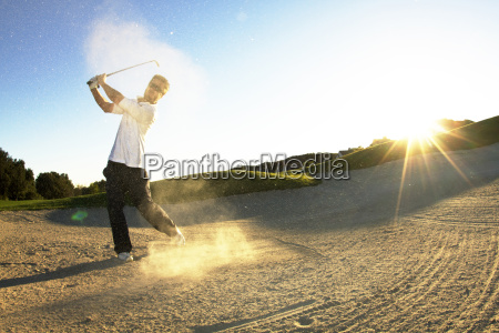 man hitting golf ball while standing