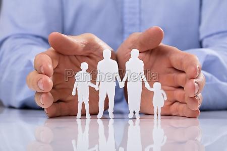 unternehmer der familie papier ausschnitt schuetzt