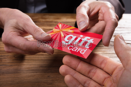 businessperson giving gift card to colleague