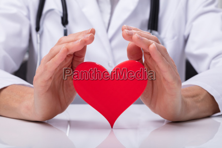 doctor protecting heart shape