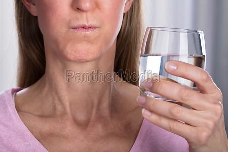 frau rinsing und gargling mit wasser