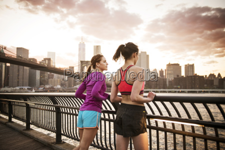 friends standing at railing by river