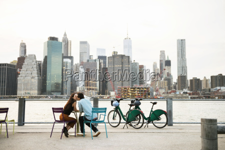 couple kissing while sitting at sidewalk