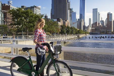 thoughtful woman with bicycle on bridge
