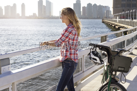 woman with bicycle standing on bridge
