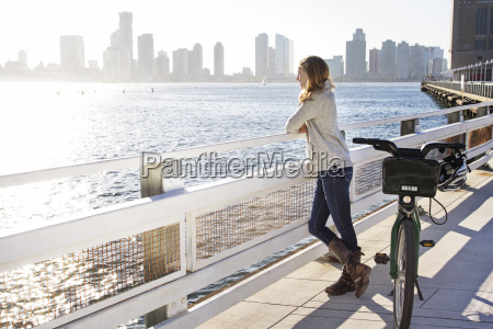thoughtful woman with bicycle standing on