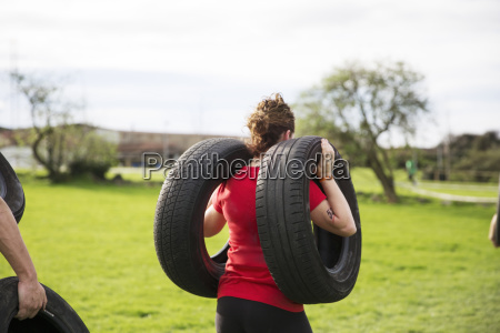 rear view of woman carrying tires