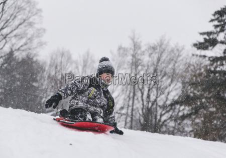 boy sitting on sled while tobogganing