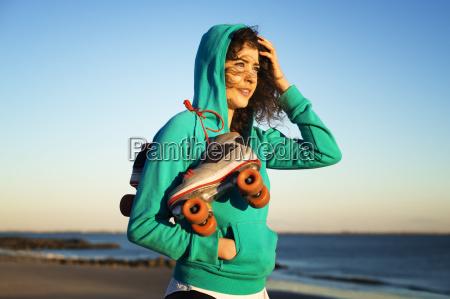 frau steht am strand mit rollschuhen