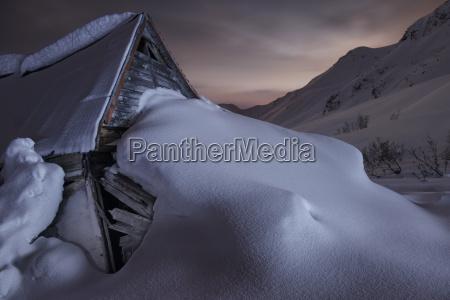 verlassener schnee bedeckte goldmine gegen himmel