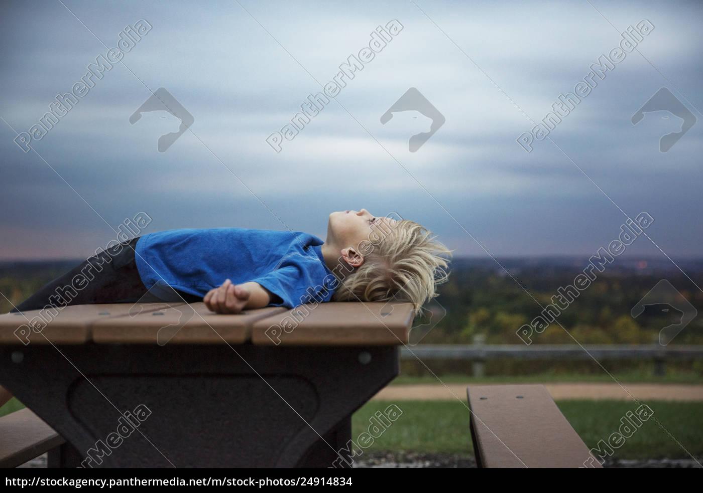 blonder, junge, der, auf, tabelle, unter, bewölktem - 24914834