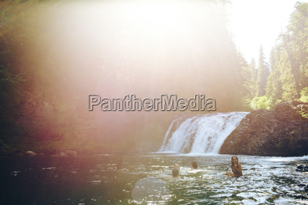 friends swimming in river at forest