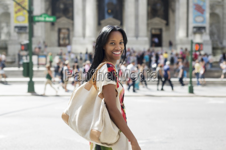 portrait of happy woman carrying purse