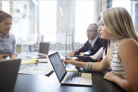 geschaeftsfraudie laptop beim sitzen mit kollegen