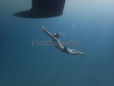 full length of man swimming towards