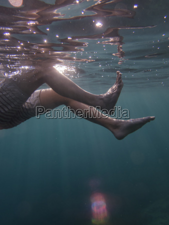 low section of man swimming underwater