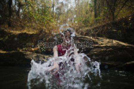 boy splashing water while enjoying in