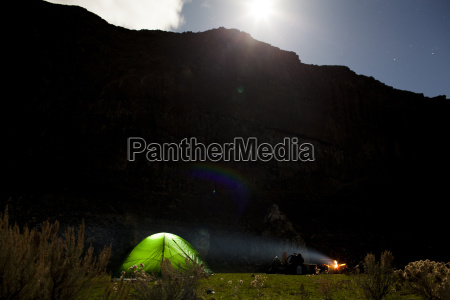 campfire by tent against mountains during