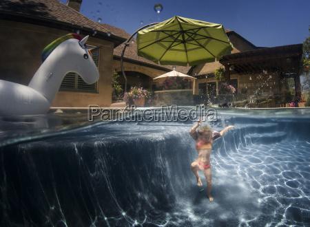 maedchendas unter wasser im pool schwimmt
