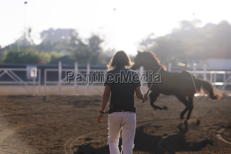 rear view of woman training horse