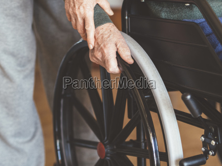 midsection of woman assisting senior man