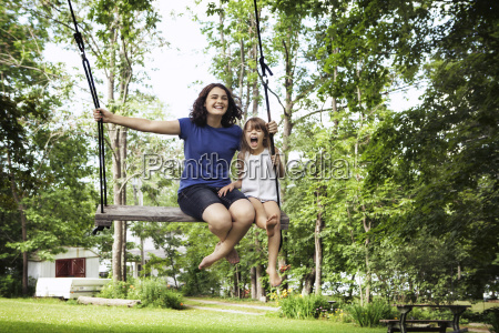 sisters playing on swing at park